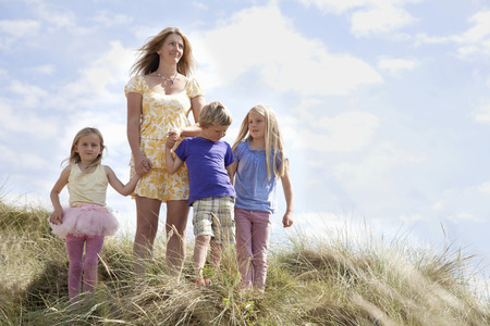 7 8: Mother with three children on dunes,Wales,UK