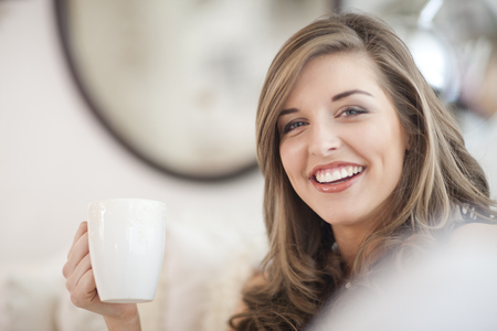 Interior room: Portrait of young woman holding coffee mug LANG_EVOIMAGES