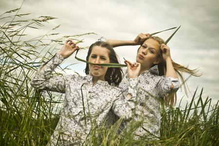 Two young women making faces with grass
