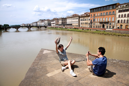 river arno: Man photographing woman with Ponte alle Grazie in background,Florence,Tuscany,Italy