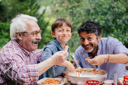 Boy enjoying a meal together with father and grandfather