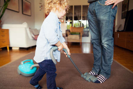 well behaved: Father teasing toddler son with hoover