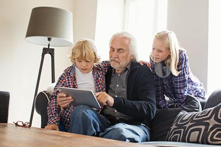 silver surfer: Grandfather using digital tablet with grandchildren LANG_EVOIMAGES