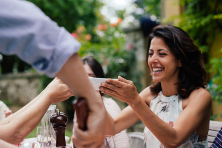 Woman holding bowl of food at outdoor meal
