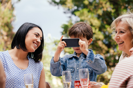 Boy taking a picture with phone at family event