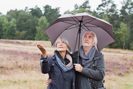 65 69 years: Senior couple under umbrella checking for rain