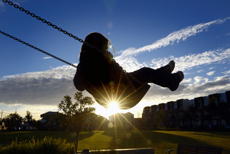 Young girl on swing at sunset LANG_EVOIMAGES
