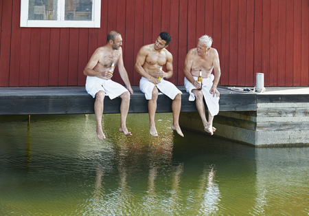 65 69 years: Three male friends sharing a beer outside sauna