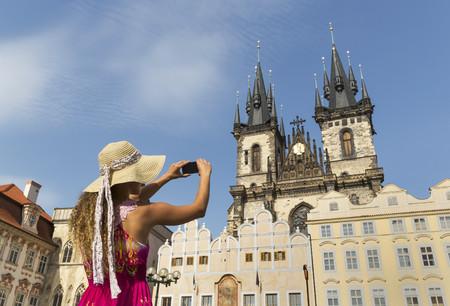 Teenage girl photographing Our Lady of Tyn church,Prague,Czech Republic