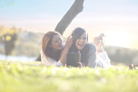 Two young women in park with digital tablet and earphones