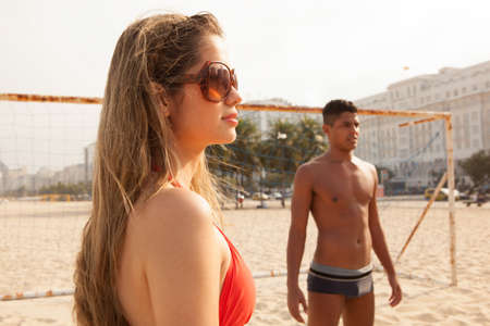 brazil beach swimsuit: Young man and woman about to play ball on beach LANG_EVOIMAGES