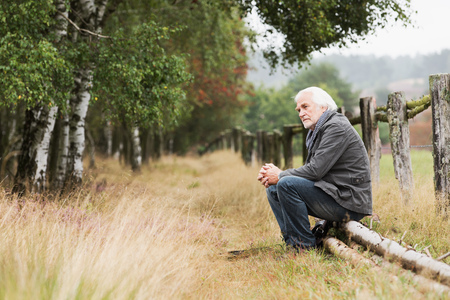Senior man sitting on log LANG_EVOIMAGES