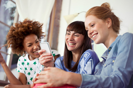 Three female friends using smartphone LANG_EVOIMAGES