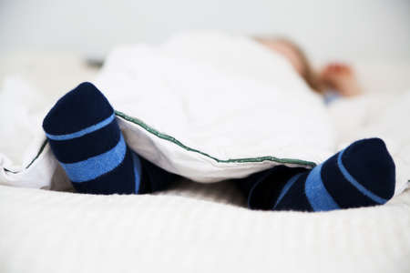 Sleeping male toddler with stripy socks LANG_EVOIMAGES