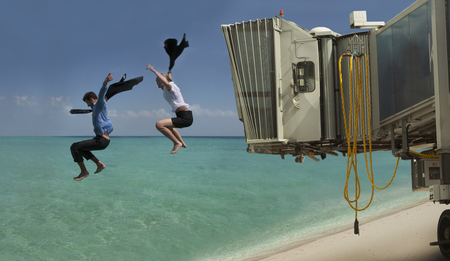 Couple jumping out of airport bridge onto seashore LANG_EVOIMAGES
