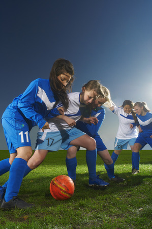 Young women playing football LANG_EVOIMAGES