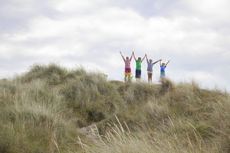 7 8: Four friends on dunes with arms out,Wales,UK LANG_EVOIMAGES