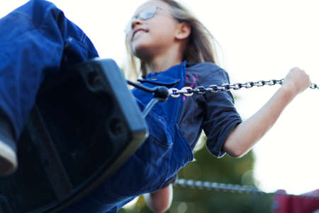 low self esteem: Young girl playing on swing in park