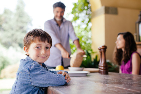 Boy at table with father and sister in background