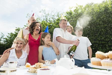 Family celebrating birthday,man opening champagne