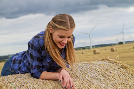 Portrait of young woman leaning over straw bale LANG_EVOIMAGES