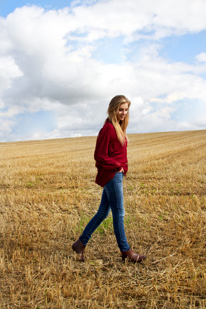 Portrait of young woman walking in harvested field LANG_EVOIMAGES