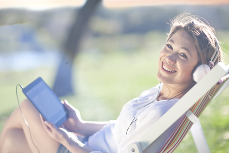 Young woman reclining in deck chair with digital tablet