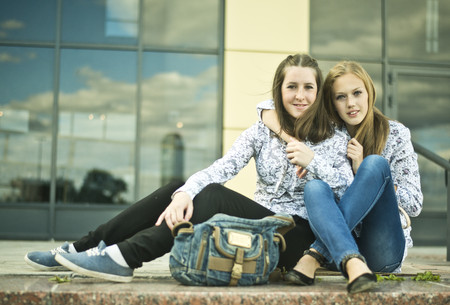 Two young women sitting together LANG_EVOIMAGES