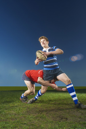 Young men playing rugby