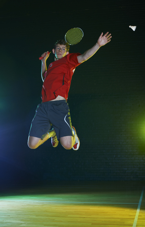 shuttlecock: Young male badminton player mid air on court