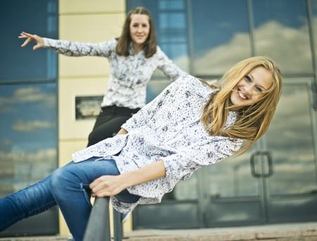 Two young women balanced on railings