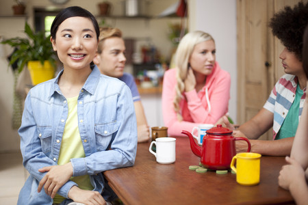 Group of young adult friends around kitchen table LANG_EVOIMAGES