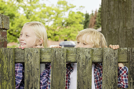 Brother and sister peering over wooden gate LANG_EVOIMAGES