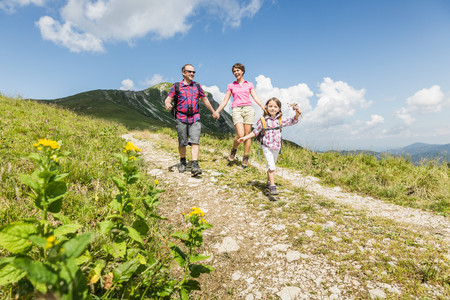 Parents and daughter walking on dirt track,Tyrol,Austria