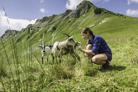 Mid adult woman with goats,Tyrol,Austria