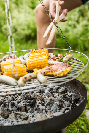 grill: Close up of young man barbecuing lunch