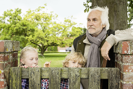 Grandfather and grandchildren by wooden gate
