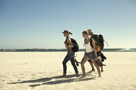 Group of young adult friends walking on beach,Cape Town,South Africa