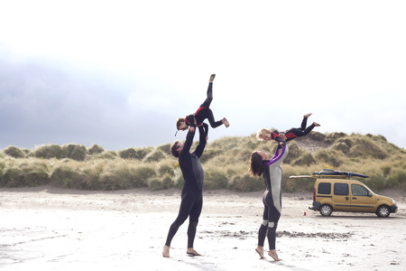 Parents lifting sons on beach LANG_EVOIMAGES