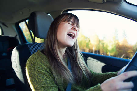 Teenage girl in car singing along to music