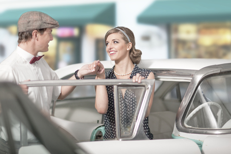 vintage: Man helping woman out of vintage car