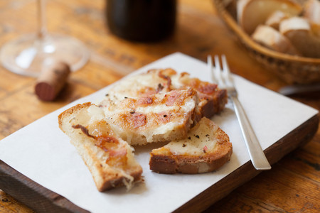Still life of toasted bread with melted cheese on chopping board