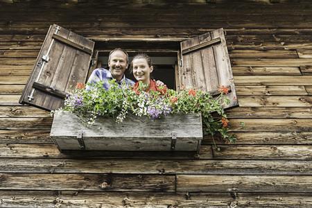 Portrait of couple at chalet window,Achenkirch,Tyrol,Austria