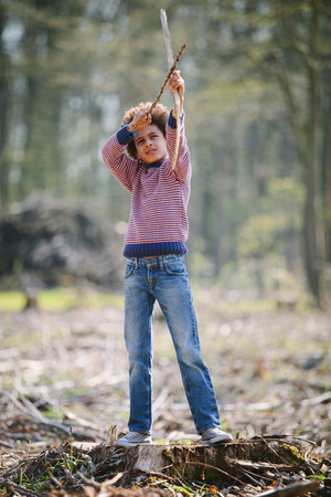 Boy aiming bow and arrow in woods