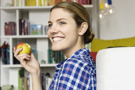leaning against: Young woman sitting on floor eating an apple LANG_EVOIMAGES