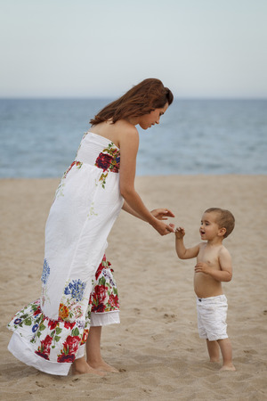 Mother and toddler standing on beach LANG_EVOIMAGES