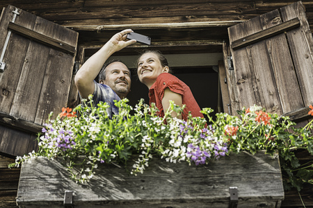 Couple taking self portrait from chalet window,Achenkirch,Tyrol,Austria LANG_EVOIMAGES