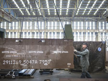 numeric: Engineer lifting steel plate in factory