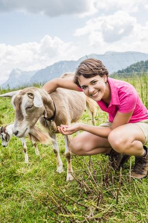 Young woman feeding goat,Tyrol,Austria