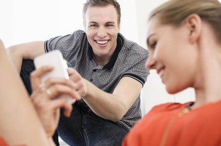 Young adult couple laughing at mobile phone LANG_EVOIMAGES